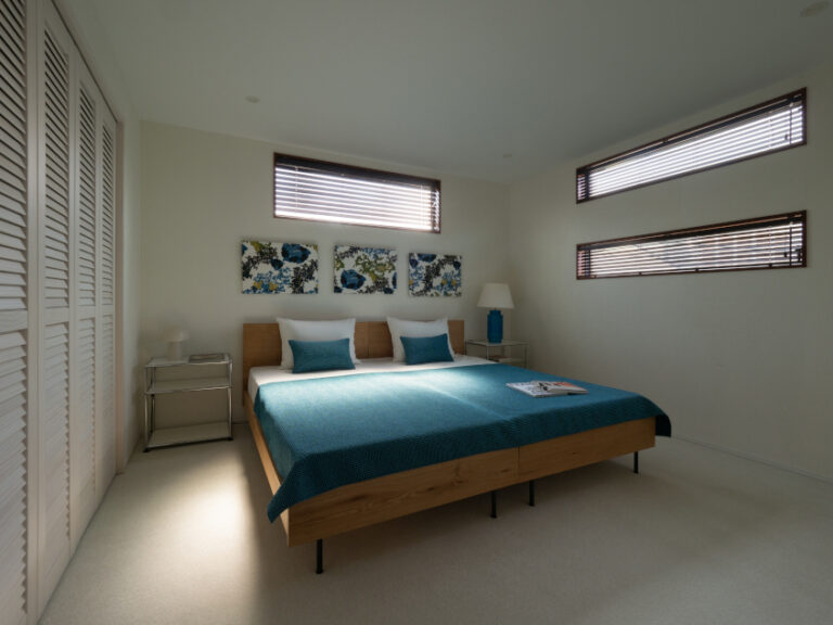 ルーバー調のクローゼット扉がリゾート感を演出する寝室。(現地モデルハウス)(寝室)